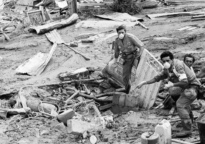 A helicopter passes, as a rescue worker points out a person at left, trapped, but alive, in mud in Armero, Colombia, November 17, 1985.