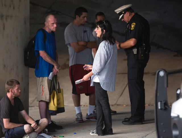Terry DeMio talks to Justin Warfield, who was in active addiction in July 2017, under a bridge downtown in Cincinnati where about a dozen homeless people with heroin addiction stayed the night.