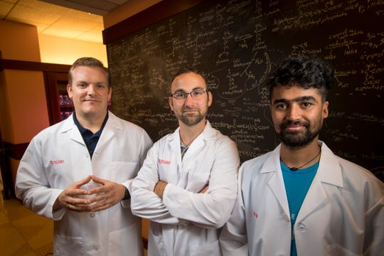 Biophysics doctoral candidate Douglas Pike (left), along with postdocs Josh Mancini (center) and Saroj Poudel, are replicating proteins from billions of years ago in an oxygen-free chamber that mimics the conditions of ancient Earth, moving one step closer to proving the origins of life.