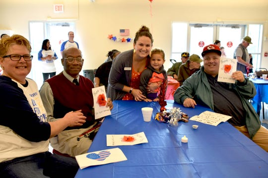 (Left to right)Tamara Schmidt, Regeneron employee; Michael Gracias, veteran; Natalie Merizio, Somerset Hills YMCA membership director with her daughter Maizie; and William Russell, veteran. The veterans, both Valley Brook Village residents, are holding up thank-you cards made by children from the Y's Early Education Center.