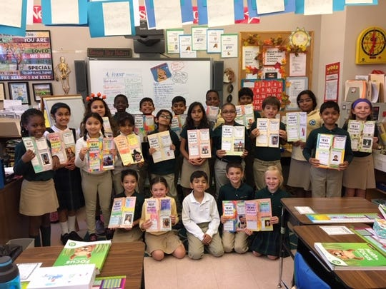 Third graders proudly display the work they shared with parents and friends.