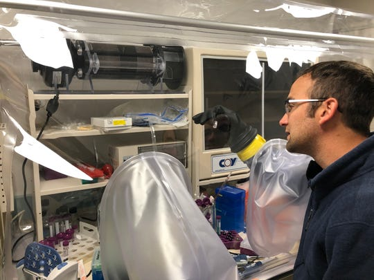 Postdoctoral researcher Josh Mancini adds nickel to proteins inside of an oxygen-free chamber that mimics the conditions of primordial Earth.