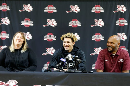 Flanked by his parents Kristi and DaJuan Foster, Oskaloosa basketball star Xavier Foster announces he's committing to Iowa State. Monday, Nov. 11, 2019.