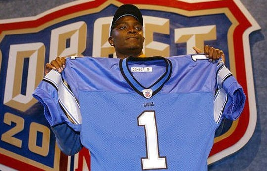 Charles Rogers holds up a Detroit Lions jersey after being selected second overall in the 2003 NFL draft.