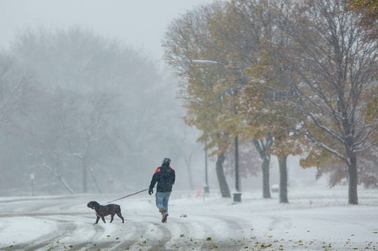 Chaz Gates of Grosse Pointe Park braves the snow with his English Bulldog Winston during their daily walk on Belle Isle as snow hit the region Monday, Nov. 11, 2019.