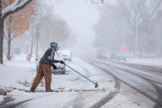 Steven Holston of Detroit helps out an aging family member by managing their snow on E. Grand Blvd. as snow hit the region Monday, Nov. 11, 2019.