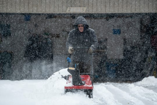 Howard Mertz uses a snow blower to remove the snow from the driveway of his home on East King William Drive in Farmington Hills, Nov. 11, 2019.