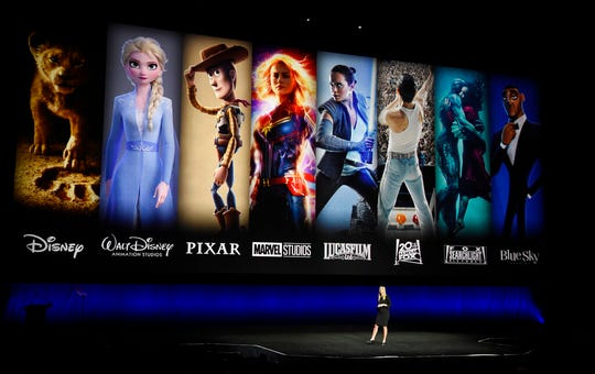 In this April 3, 2019, file photo characters from Disney and Fox movies are displayed behind Cathleen Taff, president of distribution, franchise management, business and audience insight for Walt Disney Studios during the Walt Disney Studios Motion Pictures presentation at CinemaCon 2019 at Caesars Palace in Las Vegas. On Tuesday, Nov. 12, Disney Plus launches its streaming service.