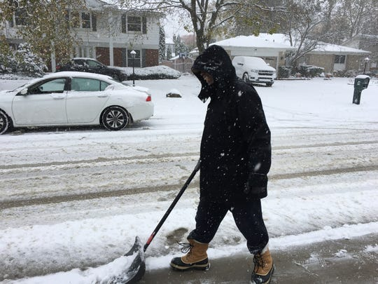 Henry Malone of Southfield clears the season's first snow outside his home on Monday, Nov. 11, 2019.