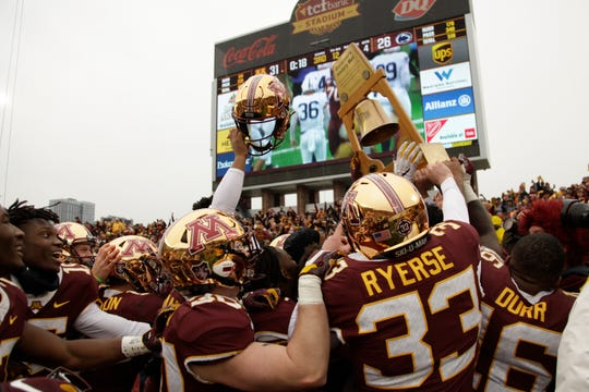 Minnesota football players hold up the Governor's Victory Bell after winning 31-26 against Penn State on Saturday in Minneapolis.