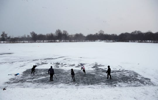 Youths play ice hockey on a frozen pond at Philadelphia's Franklin Delano Roosevelt Park during a winter storm.