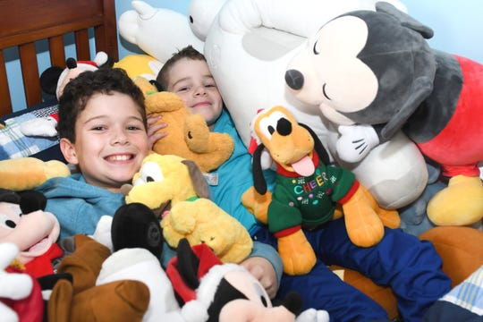 Mason Nummer, 10, left, and his brother Lucas, 7, are buried under a pile of stuffed Disney characters at their Macomb home. Their family is signing up for the Disney Plus streaming service, which launches Tuesday.
