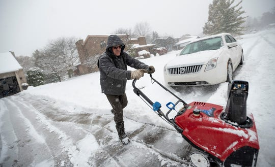 Howard Mertz uses a snow blower to remove the snow from the driveway of his home in Farmington Hills during the first heavy snowfall of the season in Metro Detroit.