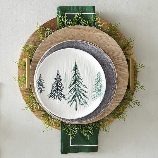 Chunky wood chargers add warmth to a setting of crackled glazes, on a gray plate topped with a textured white salad plate decorated with trees that look hand-painted, from the All Spruced Up collection at Pier 1.