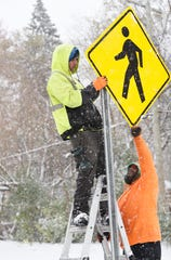 Tim Bolus, 36, top, and DeAndre Boyd, 42, install pedestrian cross walk signs in Oak Park during a steady snowfall Monday morning, November 11, 2019.