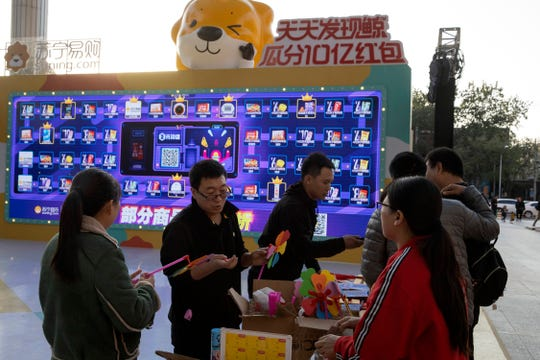 Promoters hand out free gifts Sunday as part of a game to promote Nov. 11 Singles day in Beijing.