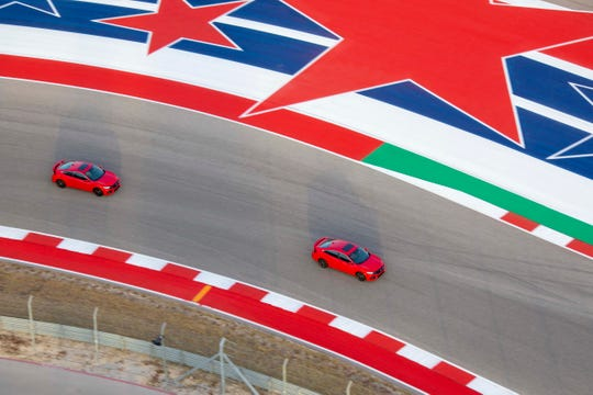 A 2020 Honda Civic Si sedan and coupe race through the Circuit of Americas' high-speed Carousel turn in Austin.