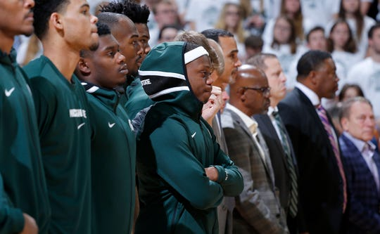 Michigan State's Cassius Winston, center, stands with teammates during a moment of silence in honor of Winston's younger brother, Zachary, before the team's NCAA college basketball game.