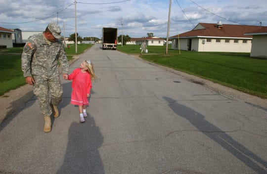 Sgt 1st Class Dan Ingler and his daughter Alaina, 4, spend a few minutes together after Ingler and other soldiers with the Evansville-based Army Reserve 406th Corps Support Battalion after returning to Camp Atterbury on Friday. The unit returned to Indiana after a tour of duty in Iraq.  Although the official homecoming is to take place next week, a few families made the trip to Camp Atterbury and were able to reunite with the soldiers.