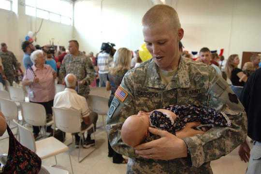 Sgt, Timothy Carrico (cq) , of the 406th Corps Support Battalion, gets to hold his two-week-old daughter Lauren (cq) for the first time at the Army Reserve Center  on their arrival back from Iraq.