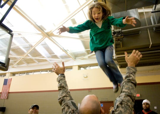 "Ashlee James, 8, elevates above the outstretched arms of her uncle, Sgt. Mark James, Thursday evening. James was nearly as ecstatic as his daughters and nieces when he arrived home from a nearly year-long tour of duty in Iraq Thursday evening. The burly soldier with the nickname ""Bull"" was happy to oblige his girls by throwing each one in turn high into the air until they were left gasping for breath."