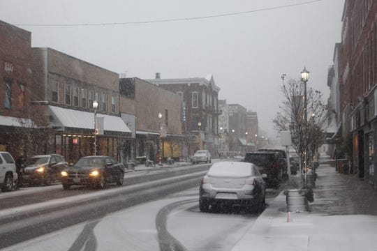 Snow covers sections of South Front Street in downtown Fremont on Monday evening, with three to five inches falling across the area overnight. A record low of 10 degrees is expected on Wednesday morning.