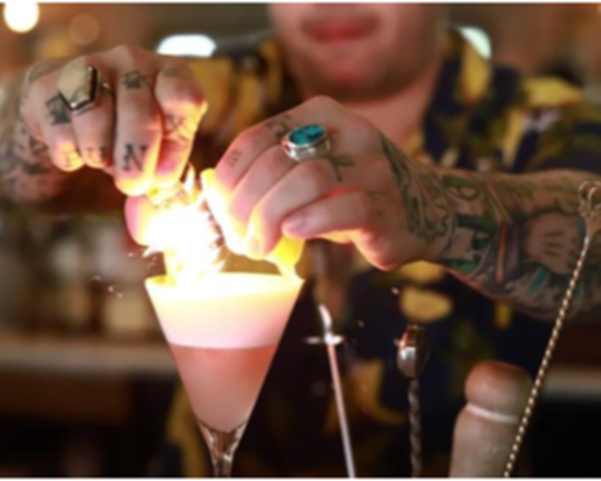 A bartender performing a flame express on a cocktail.
