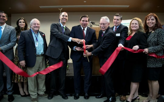 Gov. Ron DeSantis, center, joins Larry Antonucci, the president and CEO of Lee Health, in cutting the ribbon at the announcement of a program that will provide free mental health care to local veterans and military families. This was made possible by a partnership with Lee Health and Home Base Southwest Florida, a Red Sox Foundation and Massachusetts General Hospital Program.