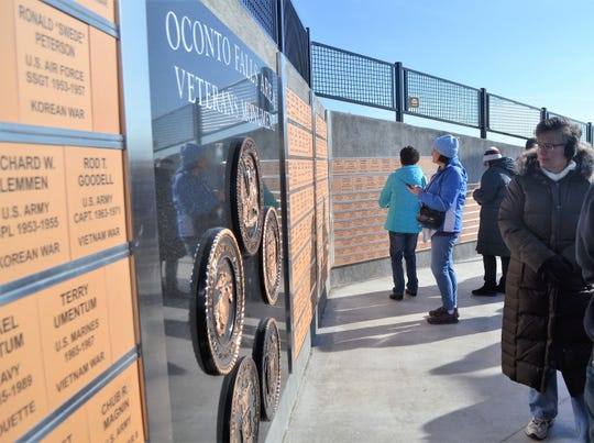 A woman looks over the center of the new Oconto Falls Veterans Monument, which contains the seals of the five U.S. military branches, following its dedication on Saturday, Nov. 9.