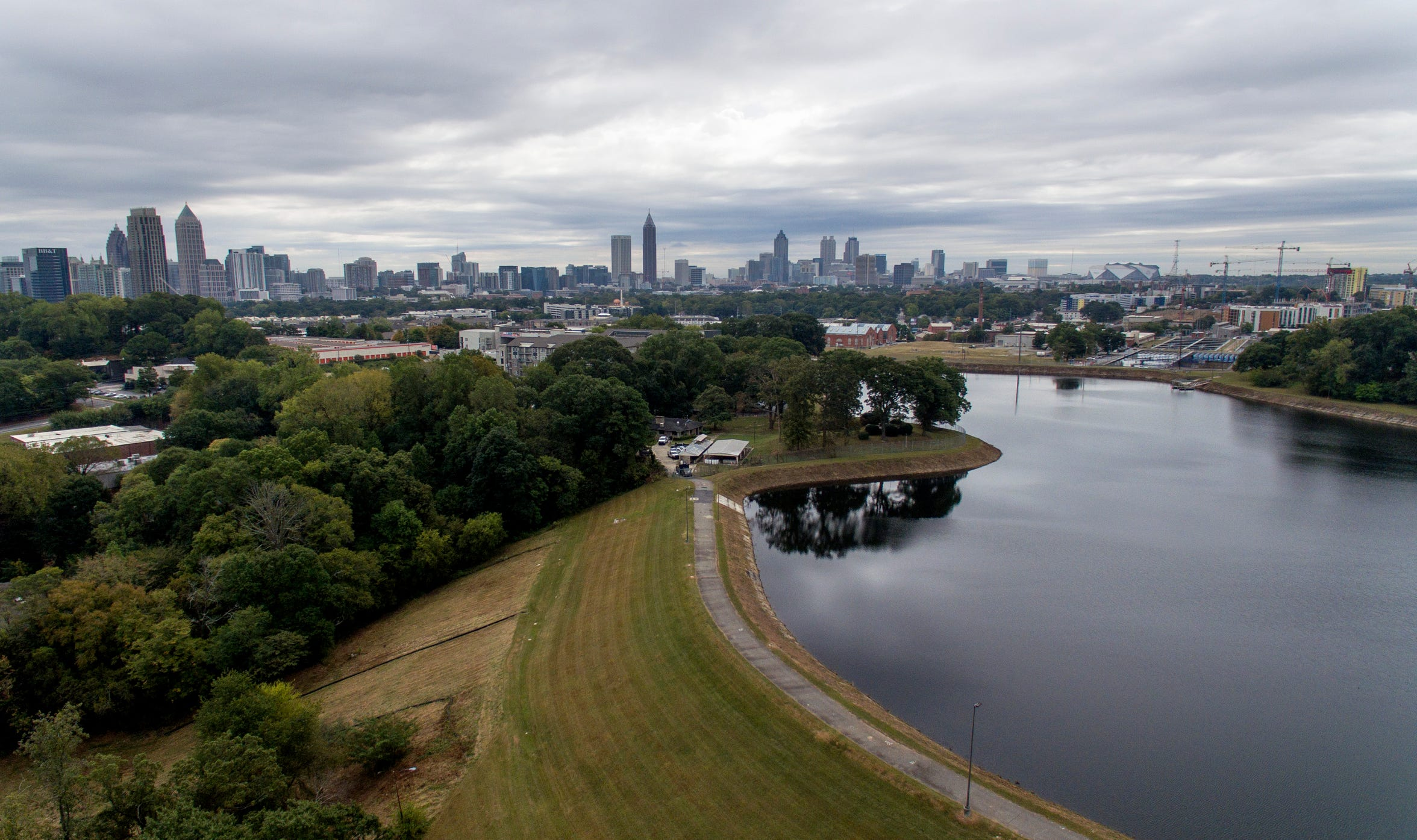 Reservoir No. 1, a 180 million-gallon water supply that has been out of service much of the past few decades, sits against the backdrop of the city skyline, Oct. 15, 2019, in Atlanta. The city made repairs and brought it back online in 2017, only to shut it down again after water leaks were noticed near businesses located beneath the dam. Were the dam to catastrophically fail, the water could inundate more than 1,000 single-family homes, dozens of businesses, a railroad and a portion of Interstate 75, according to an emergency action plan. (AP Photo/David Goldman)