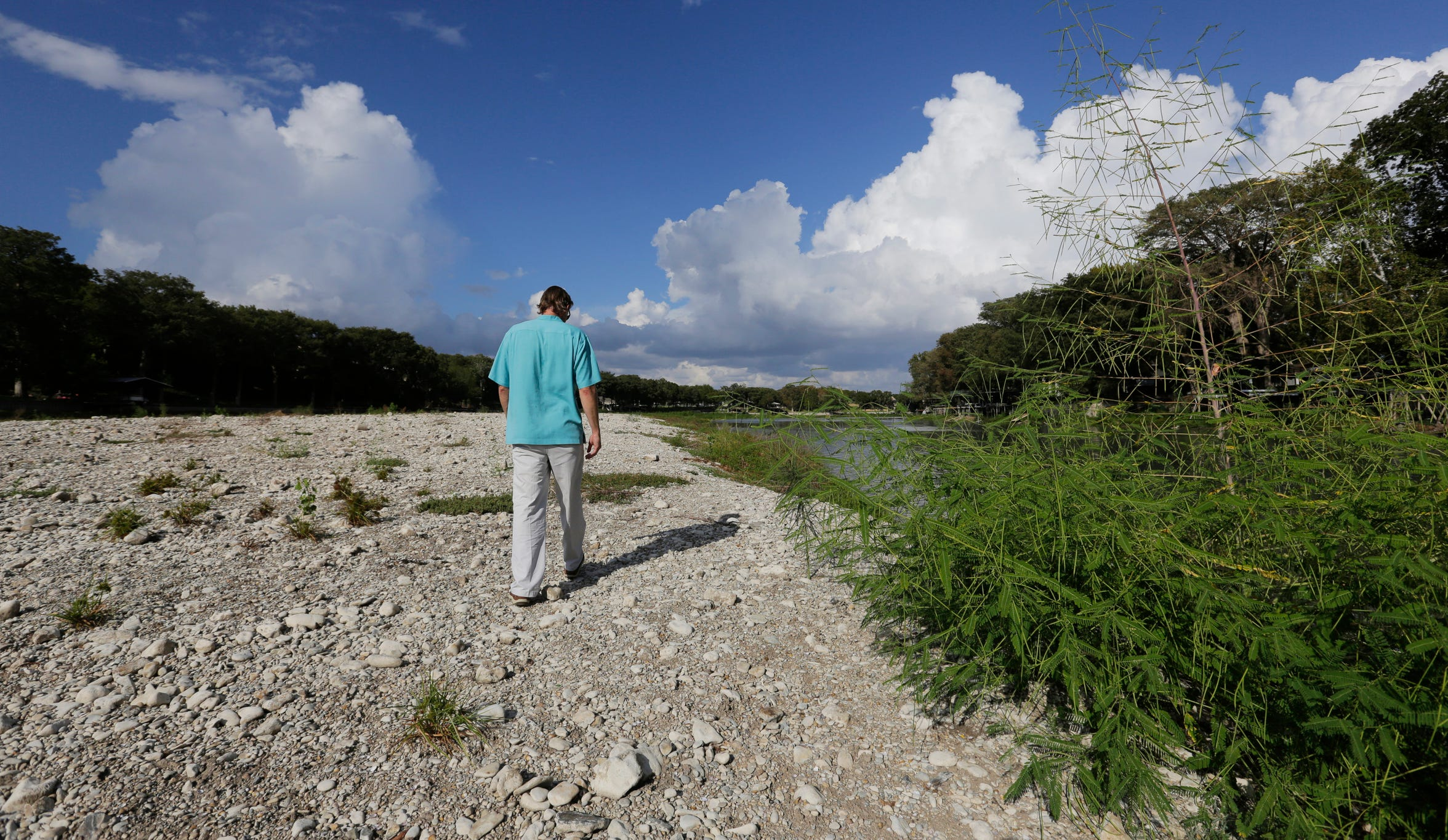 Hunter Croan walks along a dried-up section of Lake Dunlap, Sept. 30, 2019, in Lake Dunlap, Texas. Croan is one of many homeowners who were left high and dry, their lakeside docks now dry as the Guadalupe River retreated to its natural bed after the  the center spill gate of the lake's 91-year-old dam failed. (AP Photo/Eric Gay)