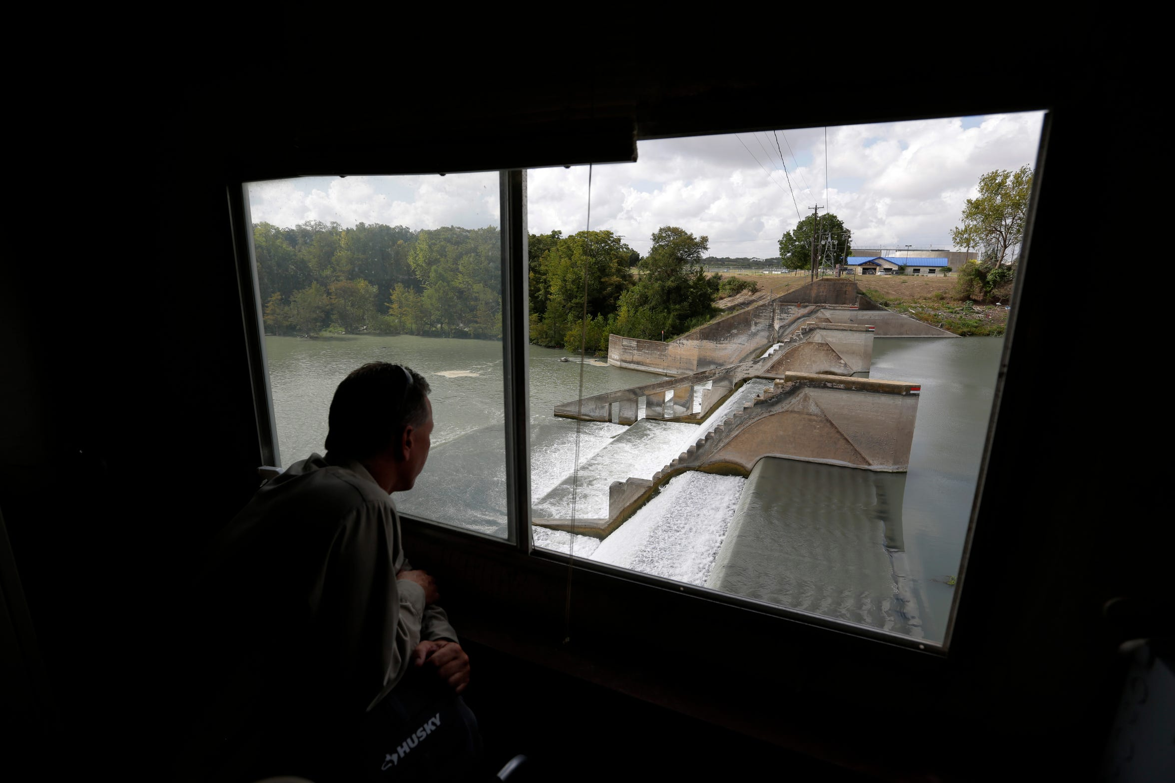 Guadalupe-Blanco River Authority's John Moryl looks over the spill gates at Lake Dunlap, Oct. 2, 2019, in Lake Dunlap, Texas. One of the spill gates at the dam failed in May and the lake drained down to the original channel of the Guadalupe River. (AP Photo/Eric Gay)