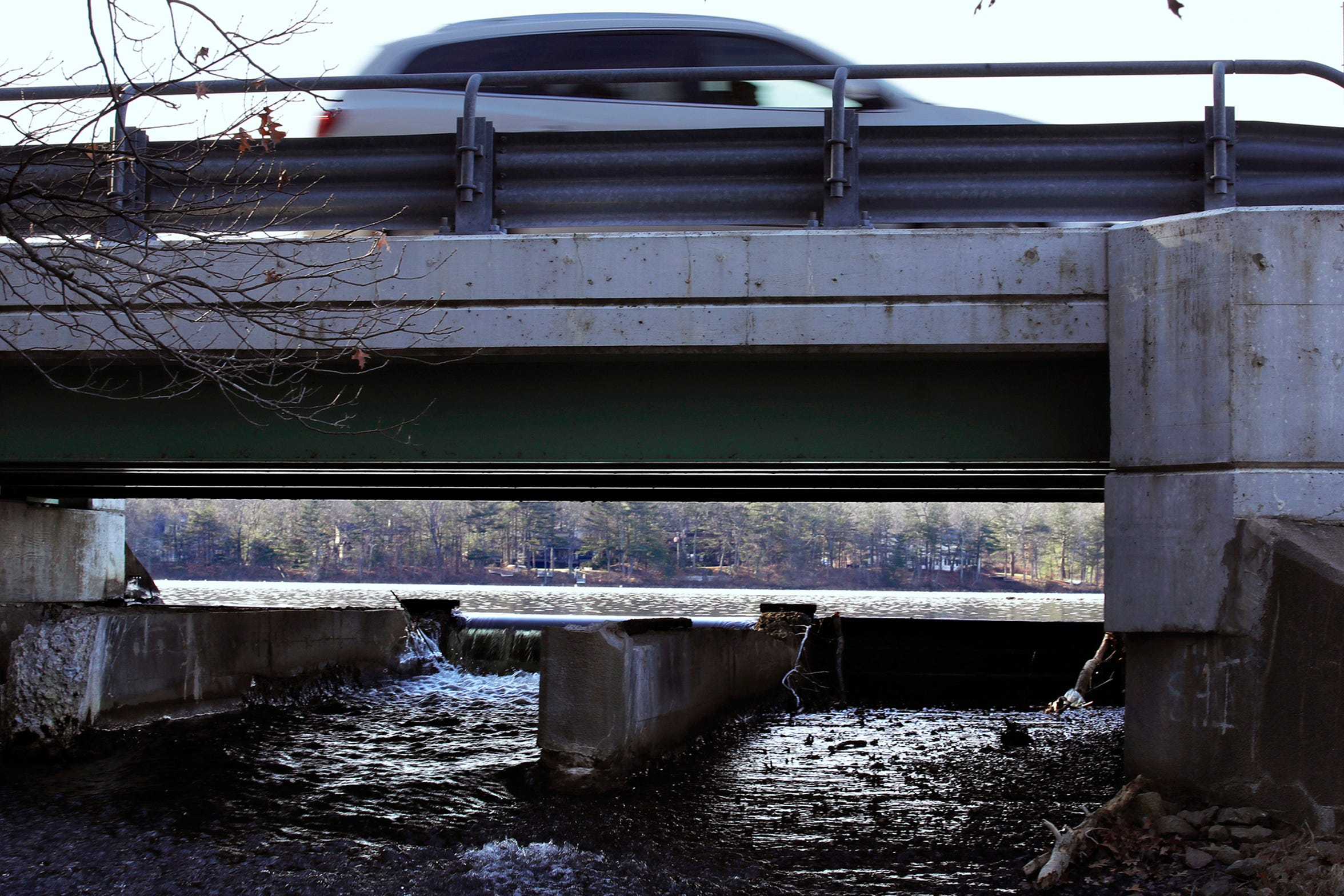 A vehicle passes over the spillway at Willett Pond on the border of Norwood and Walpole, Mass., Dec. 27, 2018. If the dam were to give way, it could send hundreds of millions of gallons of water into the heart of the Norwood, a Boston suburb of nearly 30,000 people. (AP Photo/Charles Krupa)