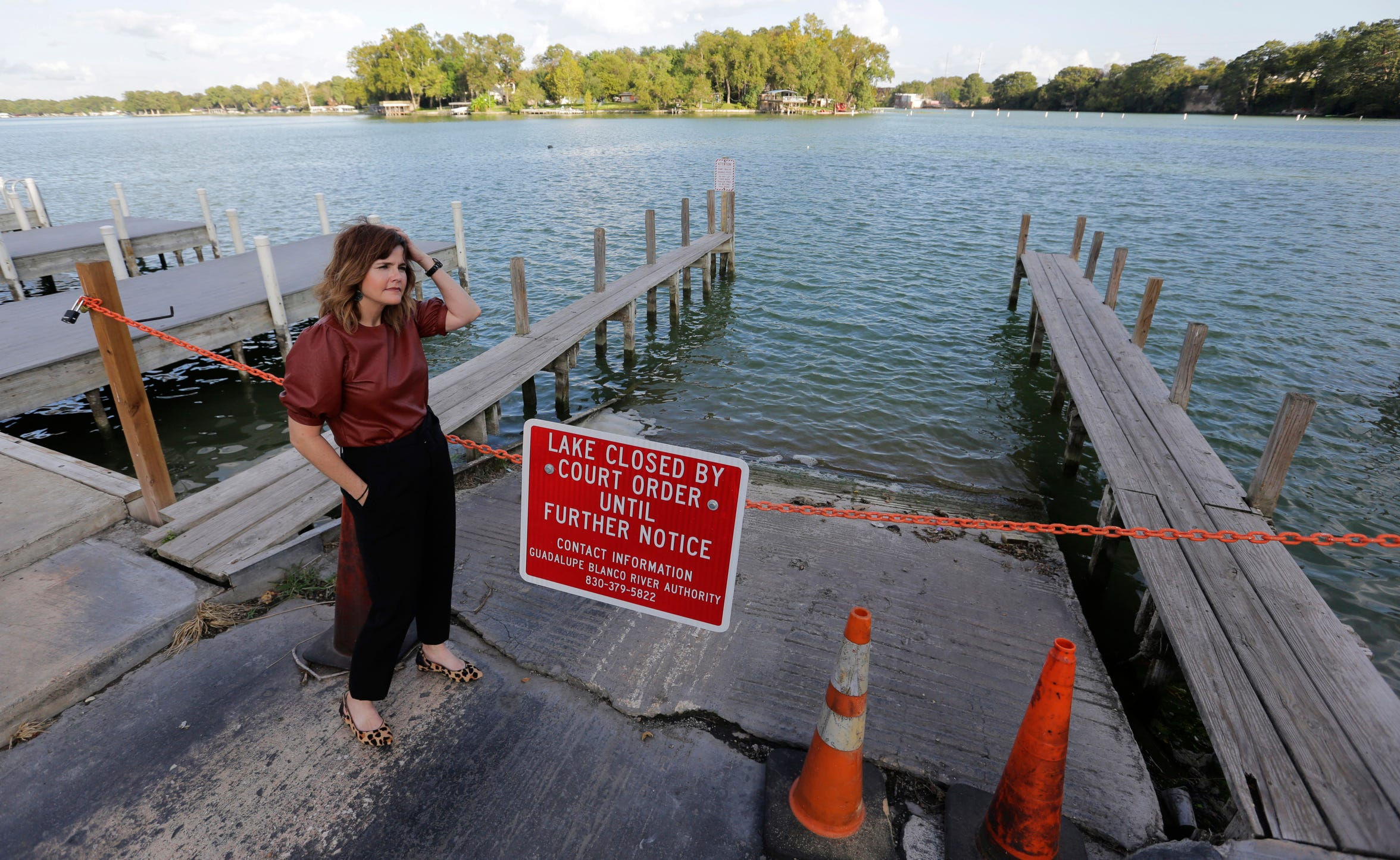 "Tess Coody-Anders, a university executive and homeowner near Lake McQueeney, one of the dams slated to be drained, stands near a sign showing the lake is closed, Sept. 30, 2019, in Lake McQueeney, Texas. ""This is something that communities and states all across the country are grappling with as we are reckoning with our aging infrastructure,"" said Coody-Anders. (AP Photo/Eric Gay)"