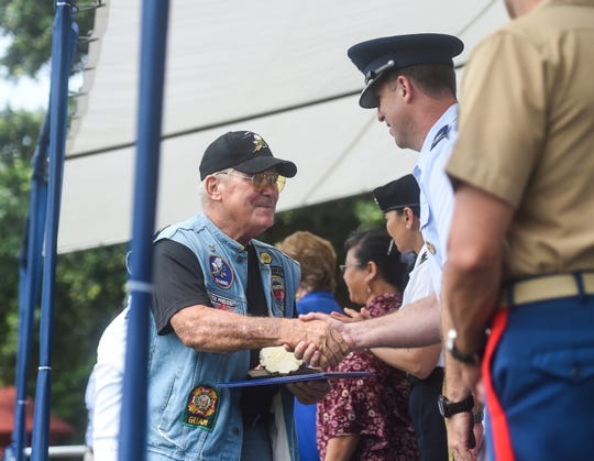 Chuck Beck, a veteran of the U.S. Navy and member of the Brotherhood of Veterans Motorcycle Club, left, is congratulated as one of the veterans of the year during a ceremony at Gov. Joseph Flores Memorial Park, Tumon, Nov. 11, 2019.