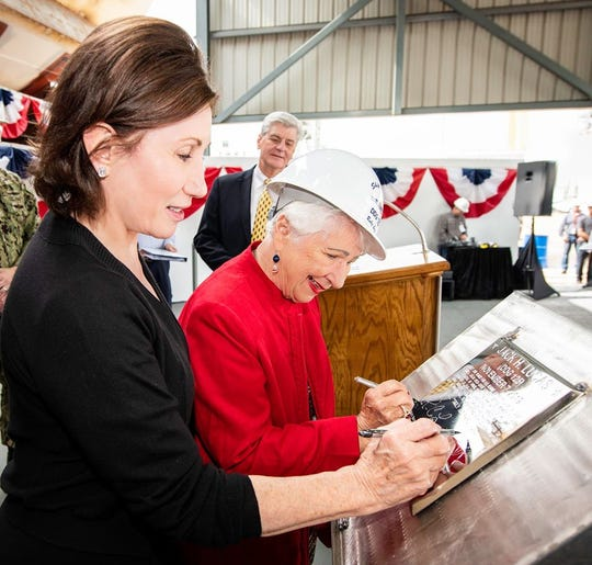 Catherine Reynolds and Ruby Lucas trace their initials onto a steel plate that will be welded inside the guided missile destroyer Jack H. Lucas. Looking on is Gov. Phil Bryant, who spoke at the Nov. 7, 2019, ceremony.