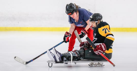 Kris Swinford helps Logan Puski to get comfortable skating on his sled during Indiana Disabled Hockey's Sled and Blind Hockey Clinic at Perry Park Ice Rink in Indianapolis on Saturday, Sept. 21, 2019.