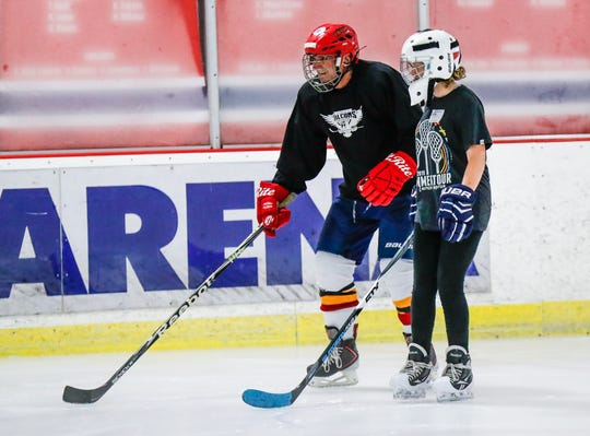James Michaels, left, skates while a volunteer encourages him during Indiana Disabled Hockey's Sled and Blind Hockey Clinic at Perry Park Ice Rink in Indianapolis on Saturday, Sept. 21, 2019.