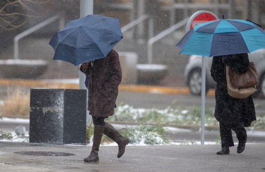 Pedestrians brave wind and a snowy afternoon in Indianapolis, Monday, Nov. 11, 2019.