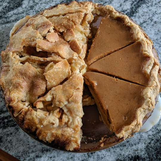 Half of an apple pie with sour cherries and half of a pumpkin pie with orange zest.