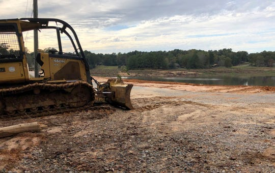 In this Nov. 4 photograph, a bulldozer rests where crews are rebuilding a dam at the Rainbow Lakes subdivision near Meridian, Miss. The dam is one of a number in Mississippi that could kill someone if it collapses and that inspectors had found to be in poor condition.