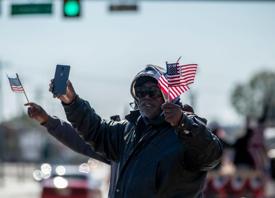 John Dixson waves the flags and records the 2019 Veterans Day parade in downtown Jackson, Saturday, Nov. 9, 2019.