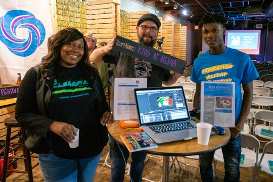 "Team ""Kids N Media"" pose in front of their project proposal as members of the community pitch their ideas to better the community at the 2019 24 Hour Citizen Project event on Nov. 9, 2019."
