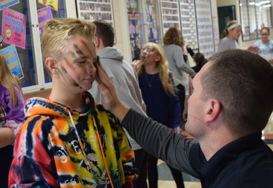 Kent Phillips, right, paints an Amanda-Clearcreek student's face during the school's Veterans Day activities. A number of veterans gathered at the school to share their experiences in the military.