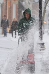 Mike Cleary, owner of Cleary's Pub in downtown Howell, clears the sidewalk in front of his establishment Monday, Nov. 11, 2019 as snow continues to fall heavily.