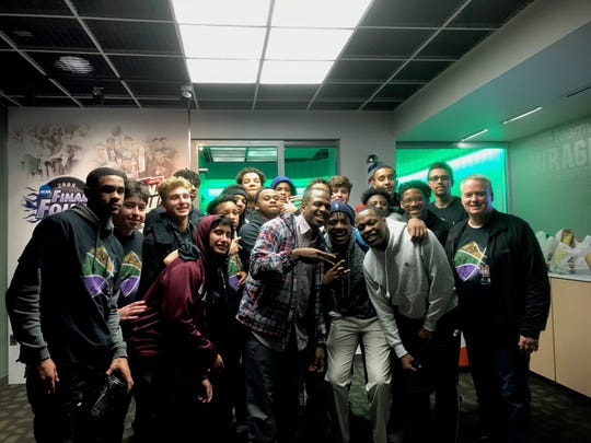 Michigan State senior point guard Cassius Winston (middle, right) poses with brothers Zach and Khy in addition to members of the basketball team at their alma mater, University of Detroit Jesuit High School.