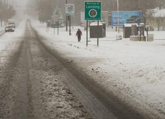 A woman walks east along Kalamazoo Street Monday, Nov. 11, 2019, as snow falls in the Lansing area.