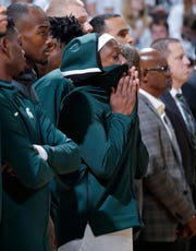 Michigan State's Cassius Winston, center, stands with teammates during a moment of silence in honor of Winston's younger brother, Zachary, before the team's NCAA college basketball game against Binghamton, Sunday, Nov. 10, 2019, in East Lansing, Mich. Michigan State won 100-47. (AP Photo/Al Goldis)