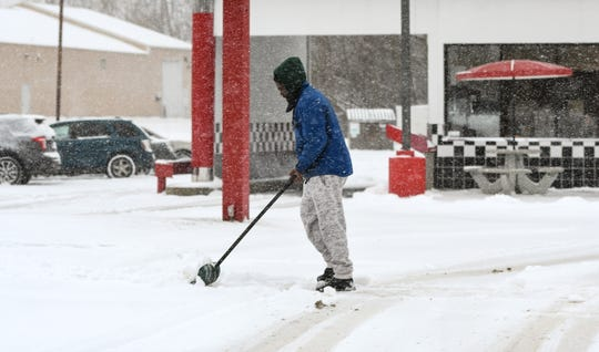A man shovels a sidewalk  Monday, Nov. 11, 2019, in front of the Rally's on Martin Luther King Blvd.