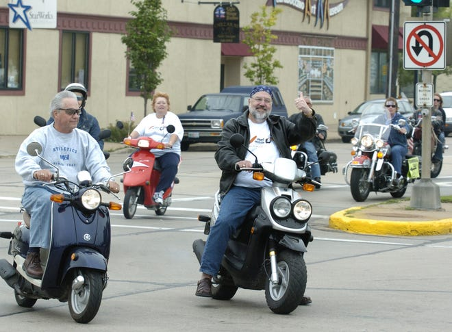 Portage County Executive Mark Maslowski, right, with the thee other members of his Scooter Brigade, lead a pack of riders in the United We Ride Motorcycle Rally on their final leg of the event kicking off Portage County's United Way 2006 campaign.